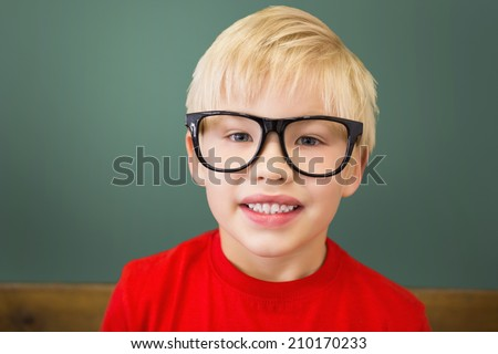 Cute pupil smiling at camera in classroom at the elementary school