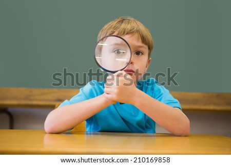 Cute pupil smiling at camera in classroom holding magnifying glass at the elementary school - stock photo