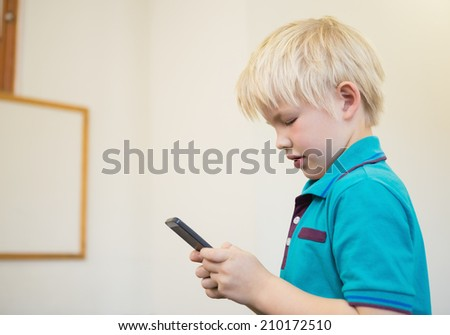 Cute pupil using smartphone in classroom at the elementary school - stock photo