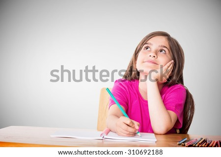 Cute pupil working at her desk against grey vignette - stock photo