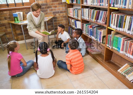 Cute pupils and teacher having class in library at the elementary school - stock photo