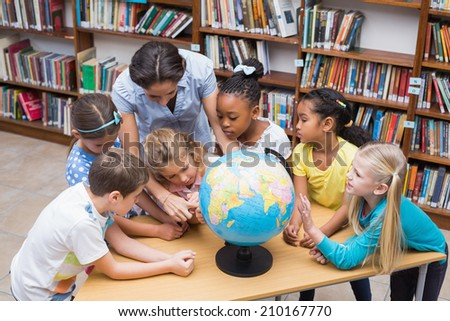 Cute pupils and teacher looking at globe in library at the elementary school - stock photo