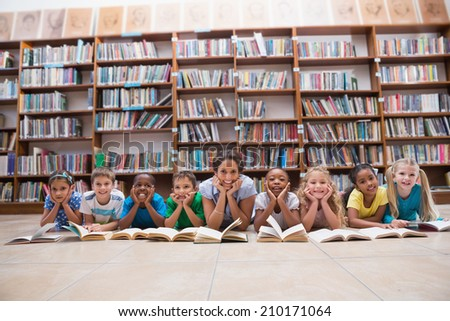 Cute pupils and teacher lying on floor in library at the elementary school - stock photo