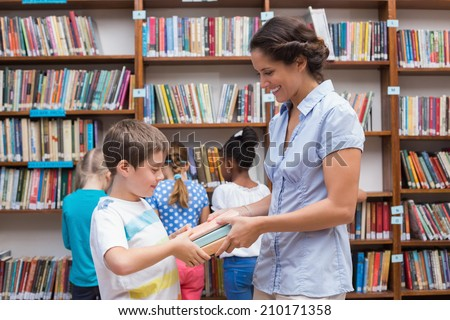 Cute pupils and teacher reading book in library at the elementary school - stock photo