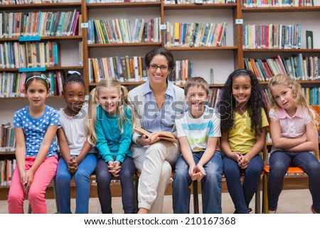 Cute pupils and teacher reading in library at the elementary school