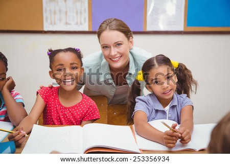 Cute pupils and teacher smiling at camera in classroom at the elementary school - stock photo