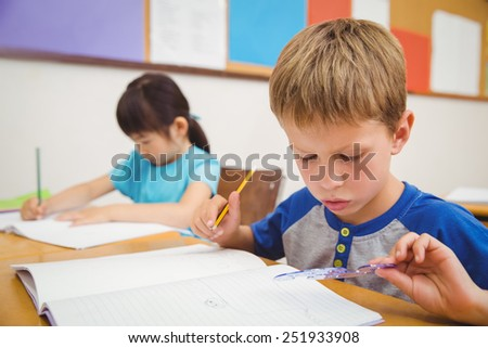 Cute pupils drawing at their desks at the elementary school