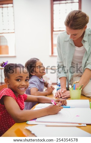 Cute pupils drawing at their desks one smiling at camera at the elementary school - stock photo