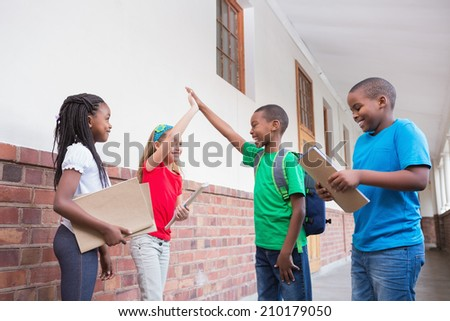 Cute pupils high fiving in the hallway at the elementary school - stock photo
