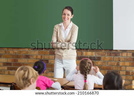 Cute pupils listening to their teacher in classroom at the elementary school - stock photo