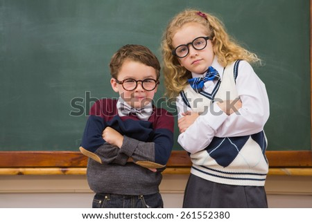 Cute pupils looking at camera with arms crossed at elementary school - stock photo