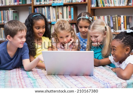 Cute pupils looking at laptop in library at the elementary school