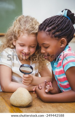 Cute pupils looking through magnifying glass at the elementary school - stock photo