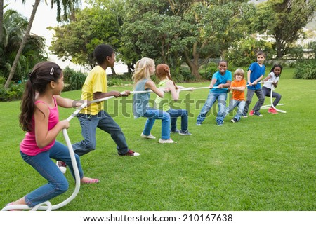 Cute pupils playing tug of war on the grass outside at the elementary school - stock photo