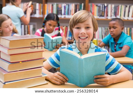 Cute pupils reading in library at the elementary school - stock photo