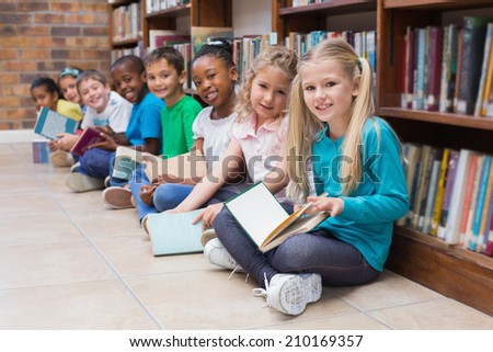Cute pupils sitting on floor in library at the elementary school