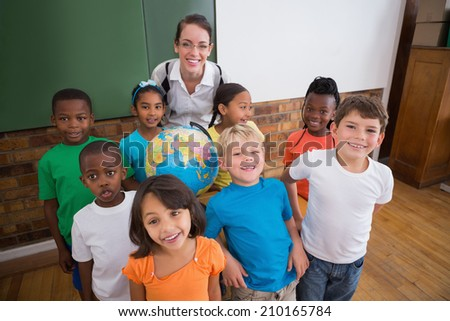 Cute pupils smiling around a globe in classroom with teacher at the elementary school - stock photo