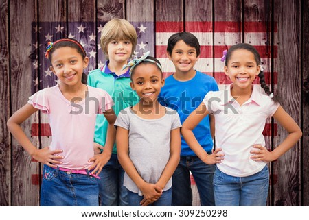 Cute pupils smiling at camera in classroom against composite image of usa national flag - stock photo