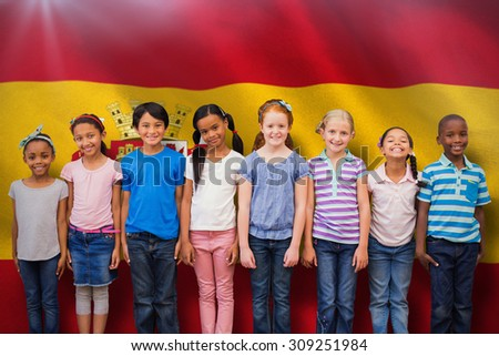 Cute pupils smiling at camera in classroom against digitally generated spanish national flag - stock photo