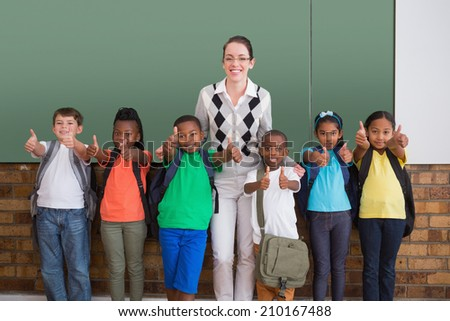 Cute pupils smiling at camera in classroom showing thumbs up at the elementary school - stock photo