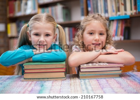 Cute pupils smiling at camera in library at the elementary school