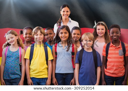Cute pupils smiling at camera in the hall against digitally generated german national flag - stock photo