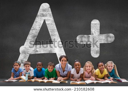 Cute pupils smiling at camera with teacher against black wall with a plus grade - stock photo