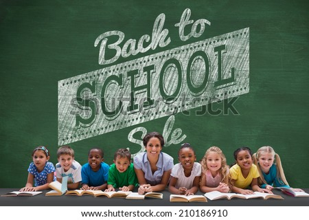 Cute pupils smiling at camera with teacher against green chalkboard with back to school message - stock photo