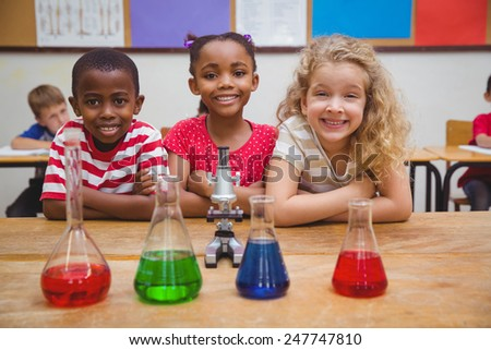 Cute pupils standing with arms crossed behind beaker at the elementary school - stock photo