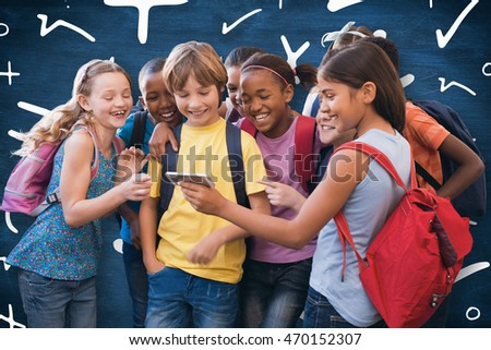 Cute pupils using mobile phone against blue chalkboard