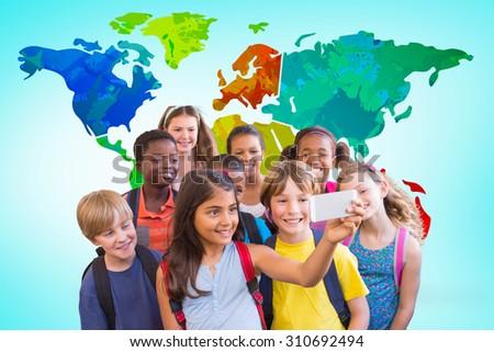 Cute pupils using mobile phone against blue vignette background - stock photo