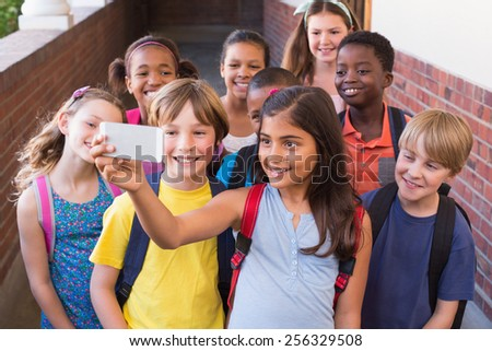 Cute pupils using mobile phone at the elementary school - stock photo