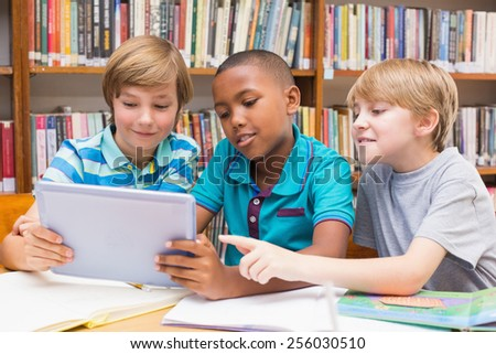 Cute pupils using tablet computer in library at the elementary school