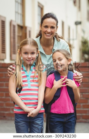 Cute pupils with their teacher on elementary school campus - stock photo