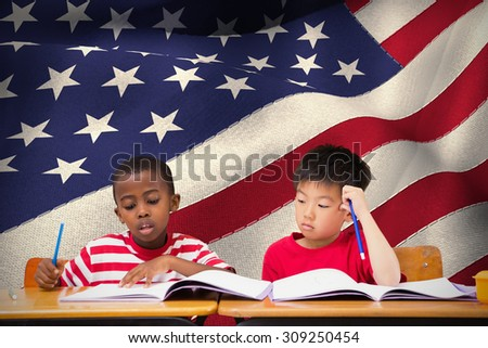 Cute pupils writing at desk in classroom against digitally generated american national flag - stock photo