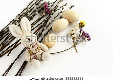cute rabbit and willow branches with buds and wooden eggs on white background, holiday card concept, easter theme - stock photo