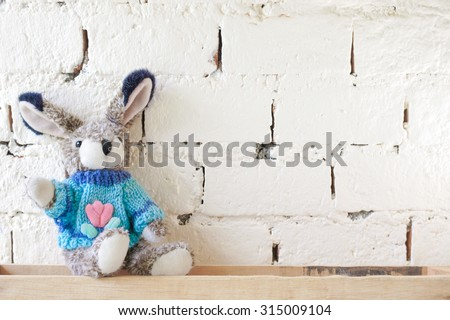 Cute Rabbit Plush Doll Wearing a Blue Sweater on Vintage Brick Wall, for Background, Wallpaper - stock photo