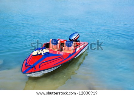 Cute Red Boat Nearby Shallow water - stock photo