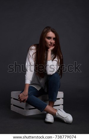 Cute red hair teenage sit on white wood cube in blue jeans and white classic shirt white sneakers