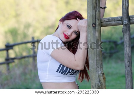 Cute redhair lady outside, bold red lips white short shirt - stock photo