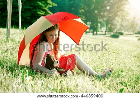 cute redhead girl with teddy bear under summer umbrella. friendship concept - stock photo