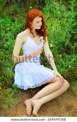 Cute redhead woman in white dress sitting on a grass in park with dandelions in her hands. - stock photo