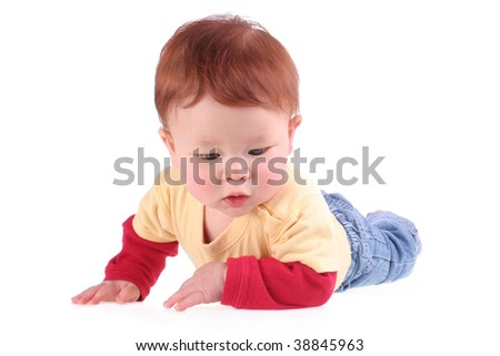 Cute, redheaded baby in yellow and red shirt, and blue jeans, laying on tummy, and isolated on white. Has clipping path.