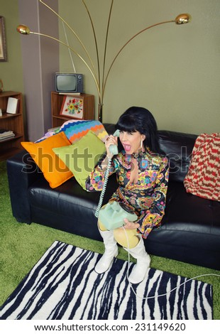 Cute retro 1970s female with telephone on sofa - stock photo