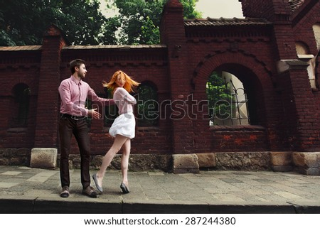 cute romantic gentle beautiful redhead stylish girl and her boyfriend spend good time in lviv - stock photo