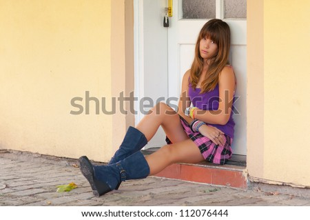 Cute sad teenage girl sitting in front of the white door. - stock photo