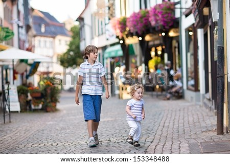 Cute school boy and his baby sister running and playing in a historical city center in Germany - stock photo