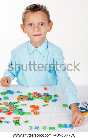 Cute school boy is playing with letters and numbers - stock photo