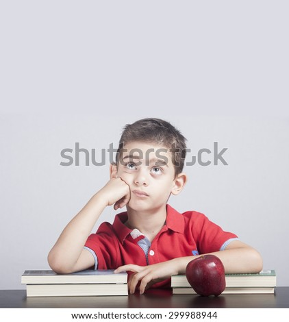 Cute school boy lost in his thoughts - stock photo