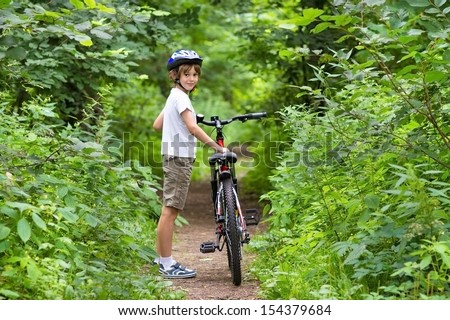 Cute school boy riding a bike in a beautiful summer park - stock photo